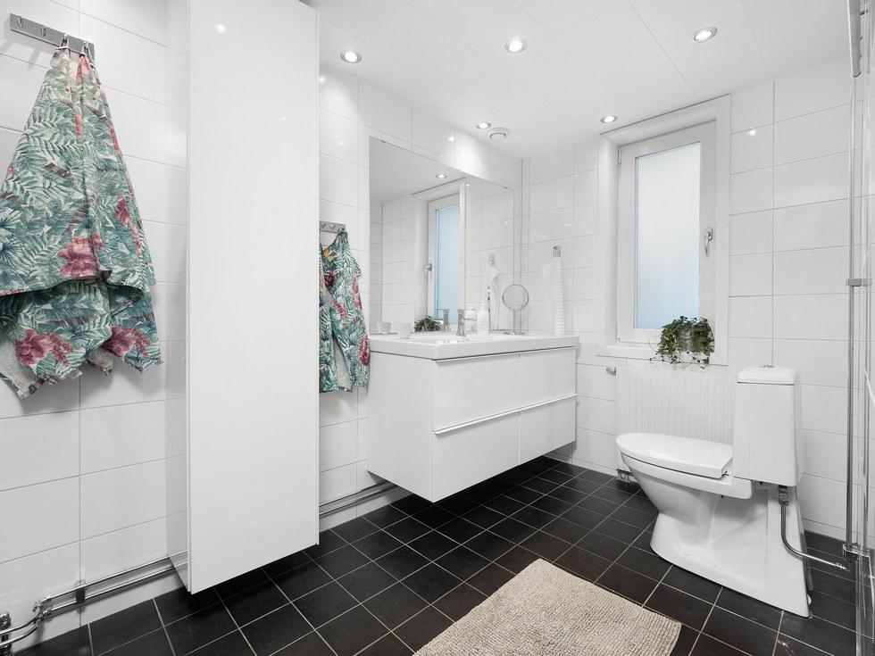 Rymligt duschrum -12 med klinkergolv, kaklade väggar och spotlights i taket