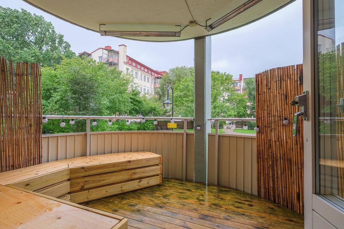 Stor balkong som vetter mot lummig innergård