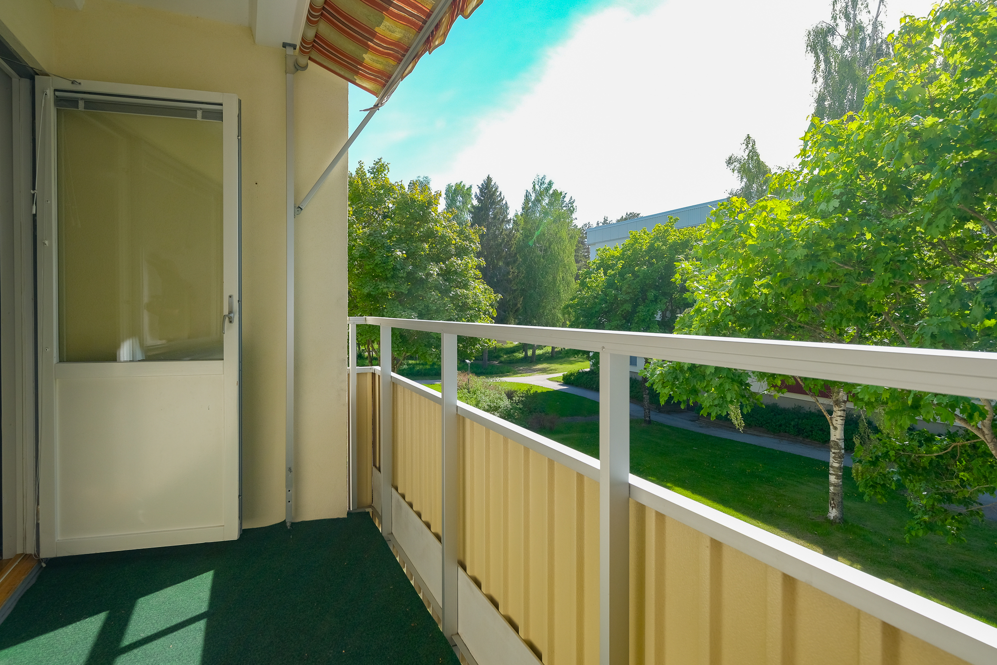 Balkong mot lummigt grönområde